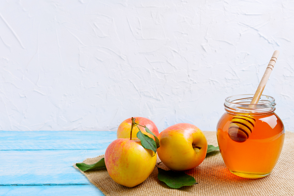 Honey jar with and apples copy space